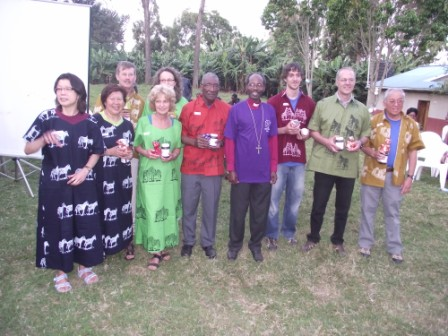 Team in Tanzanian costumes with Bishop Mwita in a T-shirt given by the team