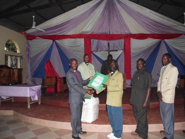 Bishop Mwita giving donated bed nets to the pastors on August 25