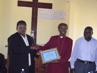 Bishop Mwita giving Dr Muniko a Certificate of Appreciation