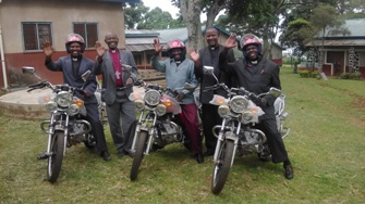 Bishop Mwita with priests on the motorcycles donated in 2016