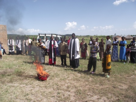 Bishop Mwita and the congregation witnessing the burning of witchcraft tools and charms surrendered by the Meng'anyi family