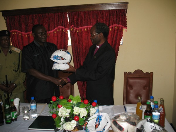 Bishop Mwita handing soccer balls to the Regional Police Commander on August 8, 2012