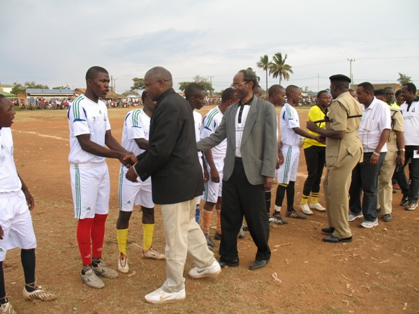 Guest of Honour, Mr Kabohola (in black jacket), Bishop Mwita & Police Commander greeting the soccer players before the inaugural match.