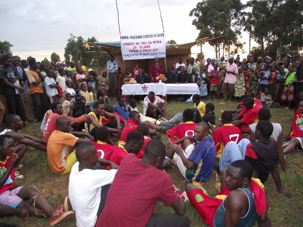 Players and the crowd listening to Bishop Mwita at Kenyamanyori Village